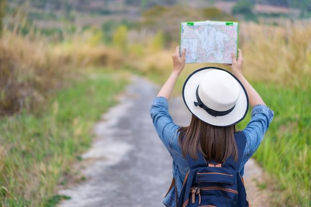 Vrouw die richting op plaatskaart zoekt terwijl het reizen