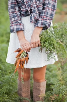 Vrouw die rijpe wortelen houdt