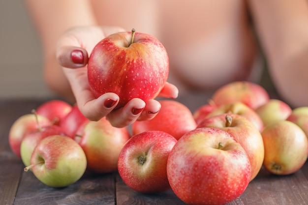 Vrouw die rode appel, ondiepe dof, nadruk op de appel aanbiedt