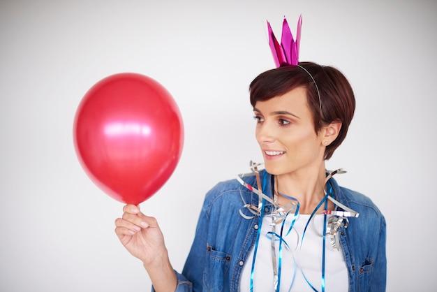 Vrouw die rode ballon bekijkt