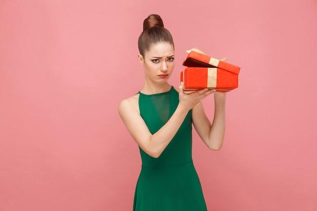 Vrouw die rode geschenkdoos uitpakt en naar binnen kijkt met een droevige blik