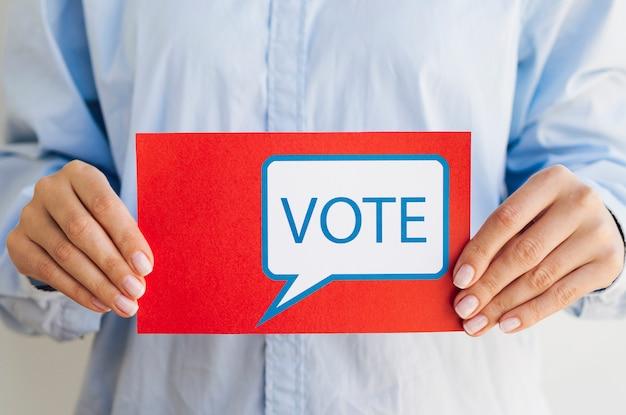Vrouw die rode kaart met de bel van de stemtoespraak houdt