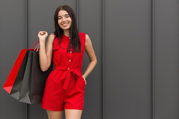 Vrouw die rode kleren draagt en zakken houdt