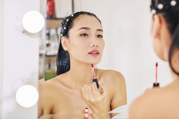 Vrouw die rode lipgloss toepast