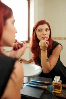 Vrouw die rode lippenstift toepast