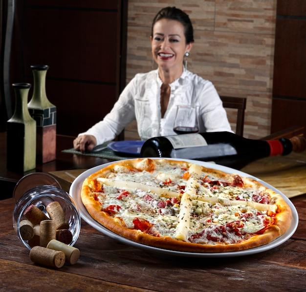 Vrouw die rode wijn drinkt en pizza eet