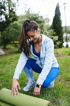 Vrouw die rolfitness of yogamat vouwt na het trainen in het park. gezond leven concept