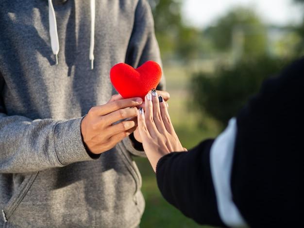 Vrouw die rood hart weigert, vormt de man. gebroken hart, liefde, valentijnsdag concept.