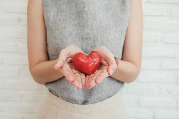 Vrouw die rood hart, ziekteverzekering, het concept van de schenkingliefdadigheid houdt