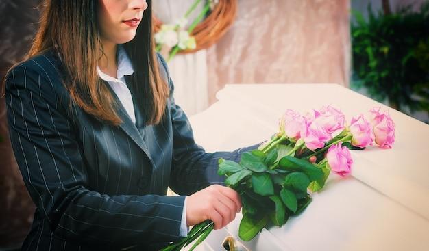 Vrouw die roos op de kist zet bij de begrafenis