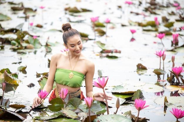 Vrouw die roze bloem in meer houdt