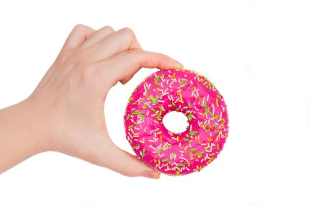 Vrouw die roze doughnut op witte achtergrond houdt. roze donut in de hand