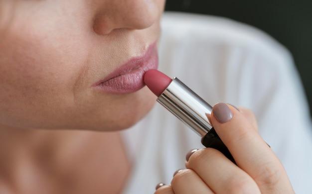 Vrouw die roze lippenstift op haar lippen toepast