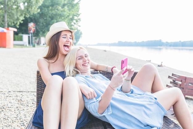 Vrouw die roze mobiele telefoon houdt die op de vriend van het wijfje bij strand leunt