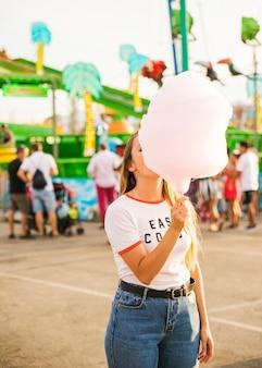 Vrouw die roze suikergoedzijde eet