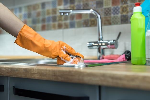 Vrouw die rubberen handschoenen draagt en de keukenkasten of het oppervlak schoonmaakt. schoonmaak concept