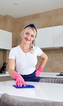 Vrouw die rubberhandschoenen draagt die lijst met doek schoonmaken. een keukentafel desinfecteren