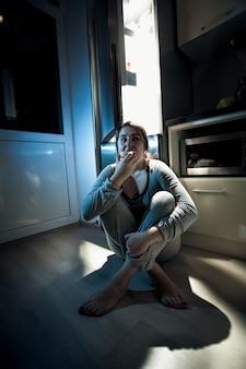 Vrouw die 's nachts donut in de keuken eet