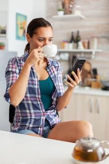 Vrouw die 's ochtends aromatische thee drinkt tijdens het browsen op smartphone
