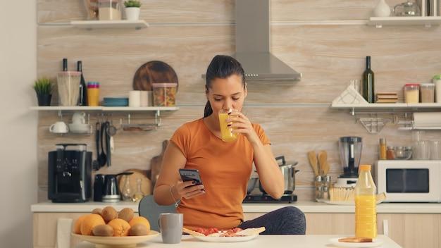 Vrouw die 's ochtends verse jus d'orange drinkt tijdens het browsen op smartphone in de keuken. huisvrouw die moderne technologie gebruikt en gezond, natuurlijk, zelfgemaakt sinaasappelsap drinkt. verfrissende ochtend