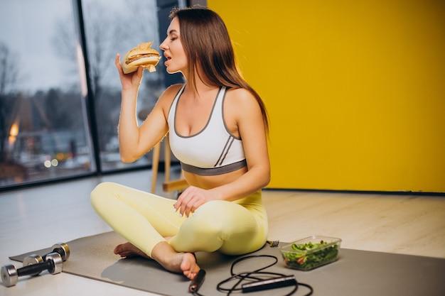 Vrouw die salade eet die op gele achtergrond wordt geïsoleerd