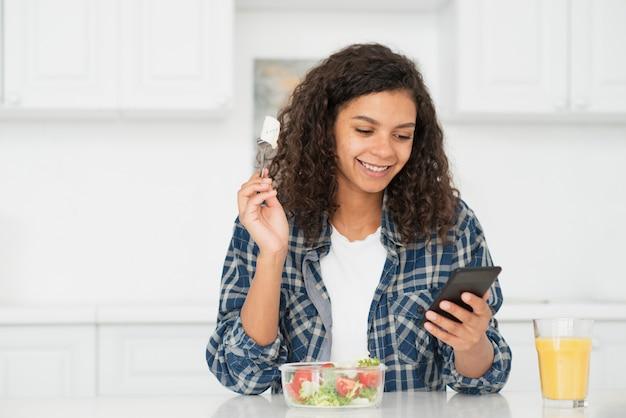 Vrouw die salade eet en op telefoon kijkt