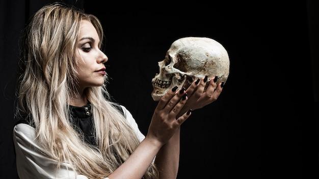 Vrouw die schedel op zwarte achtergrond bekijkt