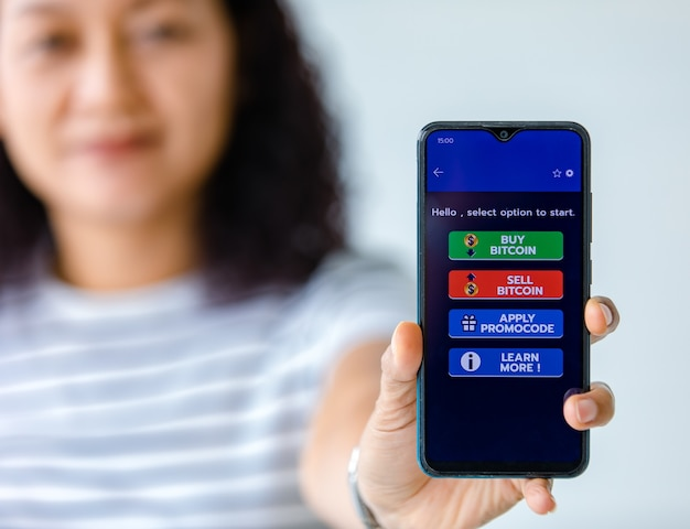 Vrouw die schermen van smartphones vasthoudt en toont met knoppen voor kopen en verkopen in een applicatie voor bitcoin of cryptocurrency digitale geldhandel.