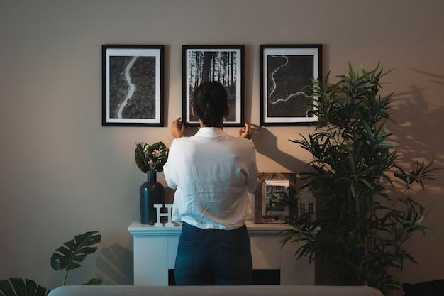 Vrouw die schilderijen thuis schikt