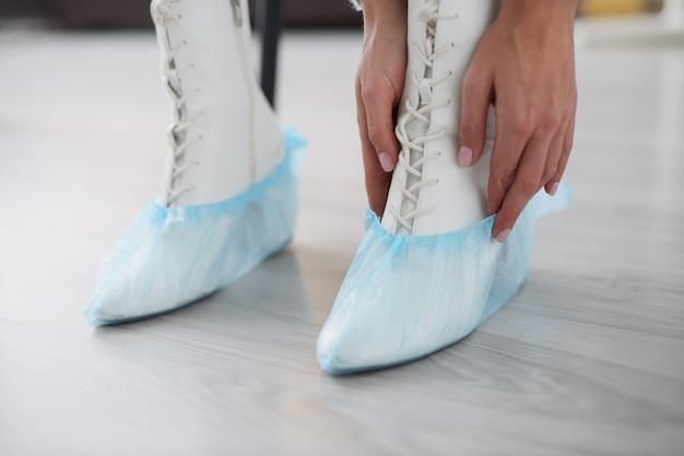 Vrouw die schoenovertrekken op haar voeten in witte schoenenclose-up zet