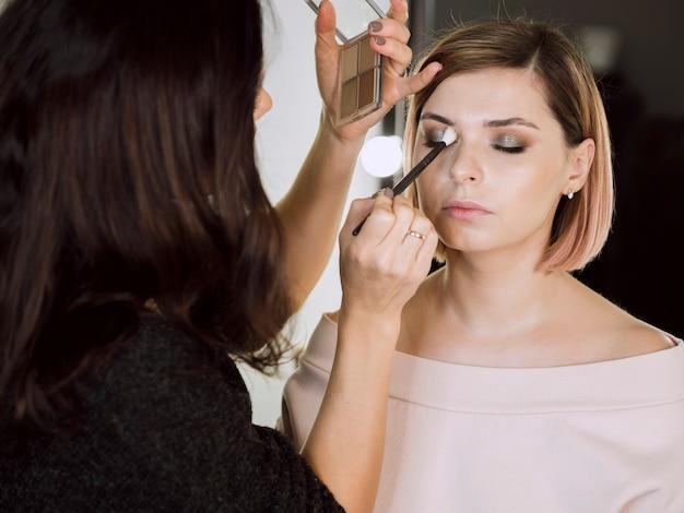 Vrouw die schoonheidsmiddelen op model toepast