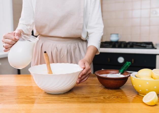 Vrouw die schort draagt die cake in keuken met ingrediënten op lijst voorbereidt