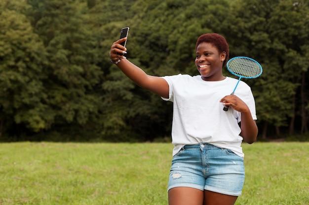 Vrouw die selfie buitenshuis met racket