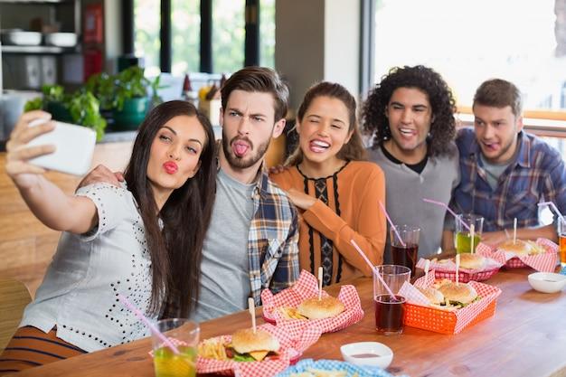 Vrouw die selfie met vrienden in restaurant