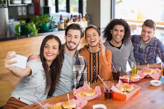 Vrouw die selfie met vrolijke vrienden in restaurant