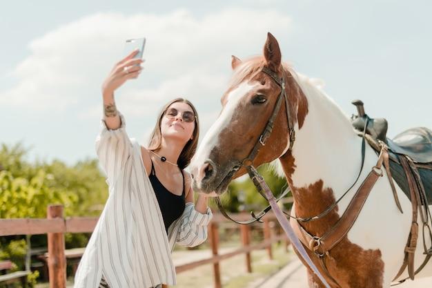 Vrouw die selfie op een telefoon met een paard op een boerderij nemen