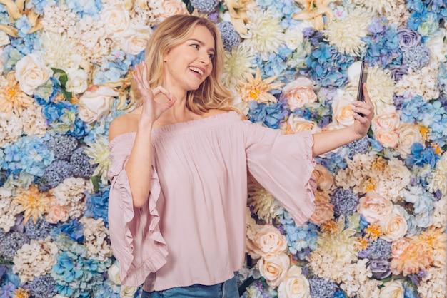 Vrouw die selfie tonend ok gebaar nemen