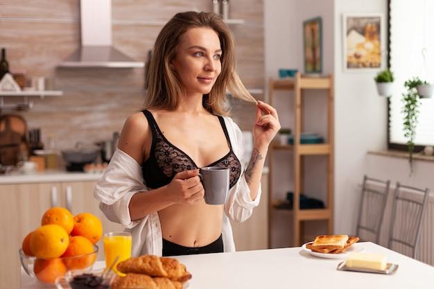 Vrouw die sexy beha draagt tijdens ontbijt in huiskeuken jonge aantrekkelijke vrouw met tatoeages in verleid...