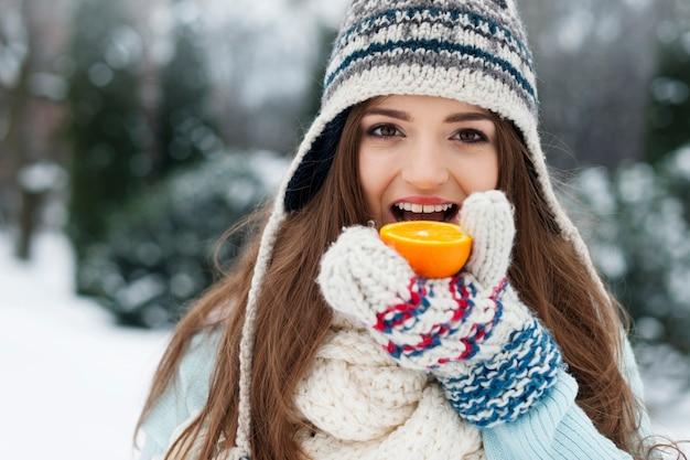 Vrouw die sinaasappel eet tijdens de winter