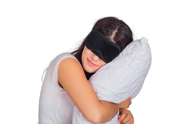Vrouw die slaapmasker draagt en een hoofdkussen houdt.