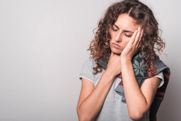 Vrouw die slaperig het hebben van koude en hoest op grijze achtergrond voelt