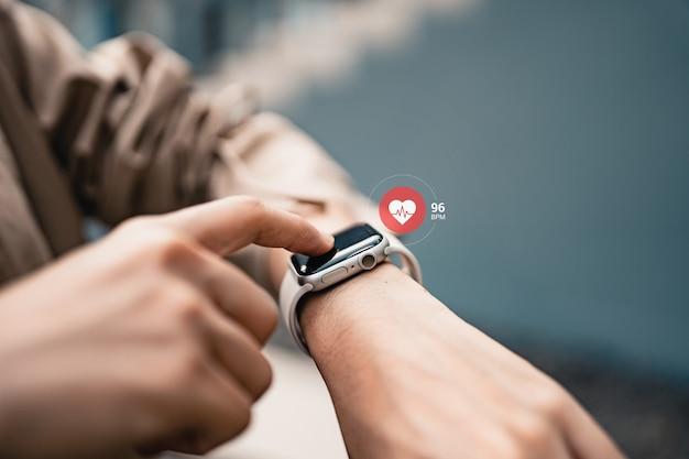 Vrouw die slimme horloges gebruikt met het controleren van de pols via gezondheidsapplicatie