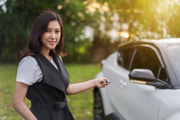 Vrouw die slimme sleutel afgelegen met een auto houdt