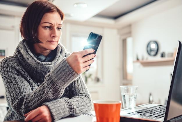 Vrouw die slimme telefoon in het bureau met behulp van