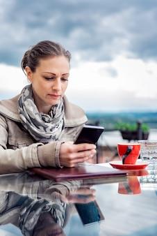Vrouw die slimme telefoon in het koffie met behulp van