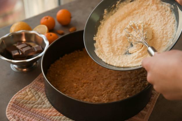 Vrouw die smakelijke cheesecake maakt, close-up