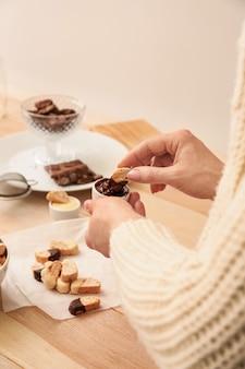 Vrouw die smakelijke italiaanse biscotti onderdompelt in saus, close-up