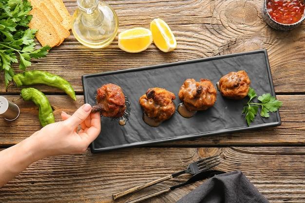 Vrouw die smakelijke kippenlollys op houten oppervlakte eet