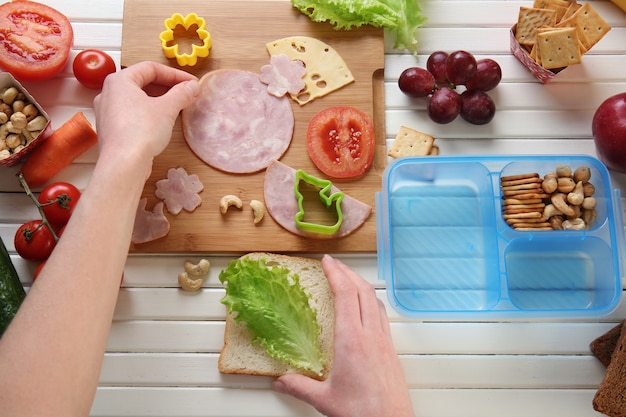 Vrouw die smakelijke sandwich op tafel maakt