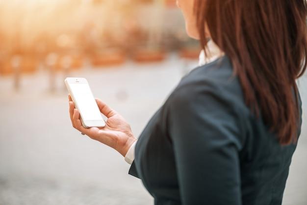 Vrouw die smartphone buiten gebruikt